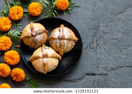 Mexican celebration, bread of death. Mexican parties with Dead bread and marigold flowers on gray stone background. Traditional Mexican Bread of the Dead Pan de Muerto . #1528192121