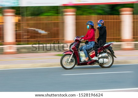 in Dong Hoi City, Quang Binh Province, Vietnam - October 11, 2019: A high quality image of people driving a motorbike on the road with panning technique #1528196624