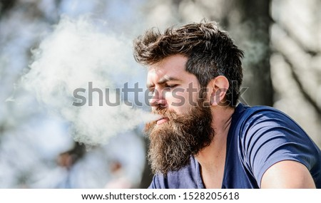 Man long beard relaxed with smoking habit. Man with beard breathe out smoke. Clouds of flavored smoke. Stress relief concept. Bearded man smoking vape. Smoking electronic cigarette. Smoking device. #1528205618
