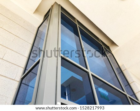 Facade of modern building with rectangular turquoise glass bay windows front view #1528217993