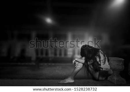 A black and white image of a young woman sitting and bowing and crying in the lonely night train station.