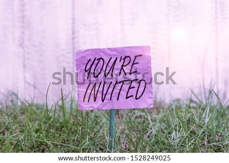 Conceptual hand writing showing You Re Invited. Business photo text Please join us in our celebration Welcome Be a guest Plain paper attached to stick and placed in the grassy land. #1528249025