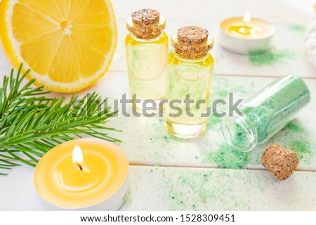 The concept of aromatherapy, relaxation, organics. Transparent bottles with aromatic oil and sea salt, spruce branch, lemon, candles on a light wooden background. Organic Apothecary #1528309451