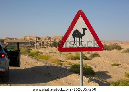 Sign with camel picture in lonely african Sinai desert and car