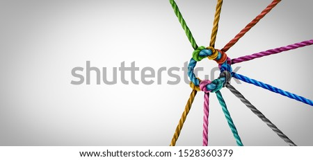 Unity and teamwork concept as a business metaphor for joining a partnership as diverse ropes connected together as a corporate symbol for cooperation and working collaboration. Royalty-Free Stock Photo #1528360379
