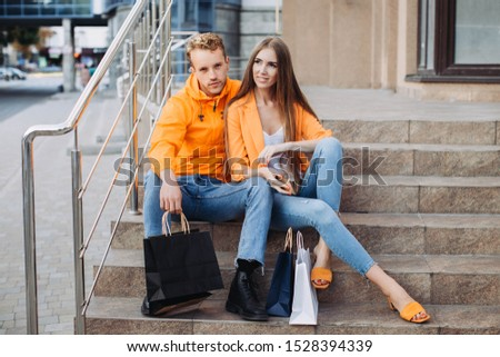 A couple of a young boy and girl in orange jackets are sitting on the stairs and chatting with bags next to them on Black Friday #1528394339
