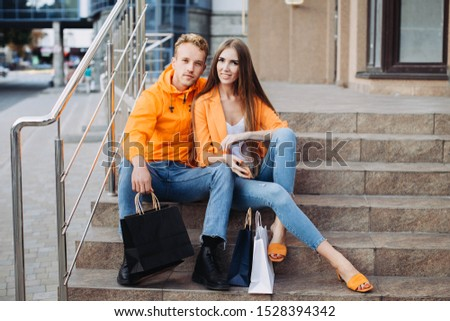 A couple of a young boy and girl in orange jackets are sitting on the stairs and chatting with bags next to them on Black Friday #1528394342