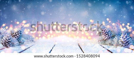 Fir Branches And Pinecones On Snowy Table And Defocused Christmas Lights  Royalty-Free Stock Photo #1528408094