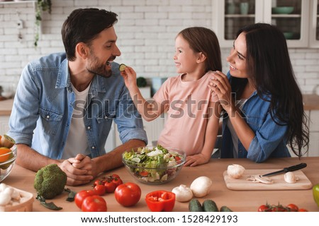 family preparing salad for lunch, daughter feeding father with slice of cucumber on the kitchen #1528429193