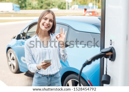 Careless and smiling young adult woman paying for charging electric car, holding modern smartphone in hand and showing ok sign. Happy girl standing near small public station against automobile