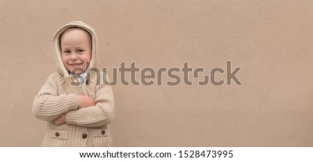 little boy 4-5 years old, in spring and winter in summer, stands backdrop of beige wall, in sweater and hood. Happy smiles, rejoices and has fun. Free space for text. Christmas background. #1528473995