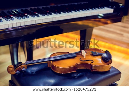 Violin and piano on wooden background. Musical instrument for learning music in music room. The music learning concept. #1528475291