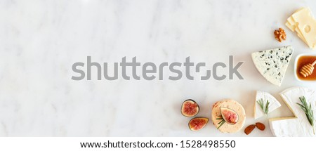 Corner border of a selection of cheeses, figs, nuts and honey. Above view banner on a white marble background with copy space. #1528498550