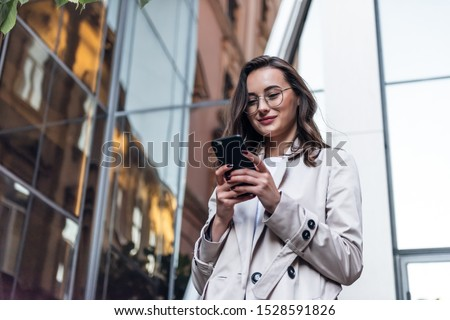 Smiling curly woman wearing trendy sunglasses walks down the central city street and uses her phone. Pretty summer woman in white jacket walks down the street looking at her mobile phone #1528591826