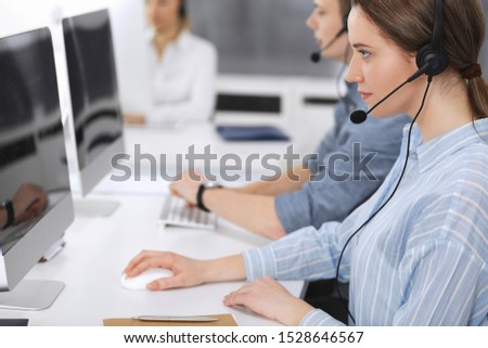 Call center. Group of casual dressed operators at work. Focus on business woman in headset at customer service office. Telesales in business #1528646567