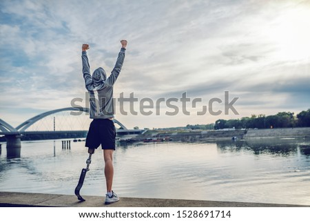 Highly motivated caucasian handicapped sportsman in sportswear and with artificial leg standing on quay and holding arms up. Only way to win is to be yourself. Royalty-Free Stock Photo #1528691714