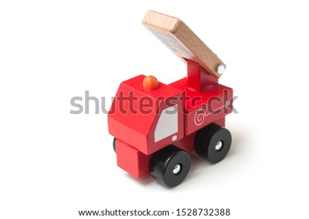 Closeup of miniature toy, wooden fire truck on white background