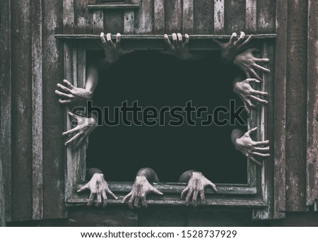 Hands rising out from the old window ancient house, Halloween concept. #1528737929