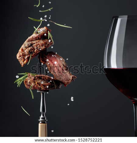 Grilled ribeye beef steak with rosemary and red wine on a black background. Beef steak on a fork sprinkled with rosemary and sea salt.    #1528752221