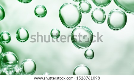 transparent gas bubbles on water surface. Worms-eye low angle with crystal bubbles in purified water on green background. cosmetic backdrop with copy space #1528761098
