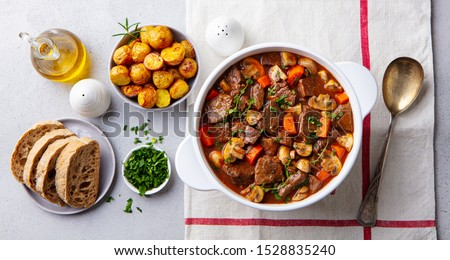 Beef bourguignon stew with vegetables. Grey background. Top view. #1528835240