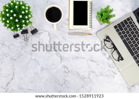 Top view desk ,Modern office desk Workplace with laptop computer, coffee cup, glasses,notebook and office supplies for Working background concept. #1528911923