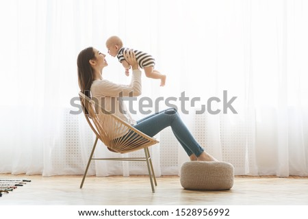 Let's fly. Beautiful mom lifting her adorable newborn child up in the air while sitting in modern woven chair, relaxing at home together, copy space #1528956992