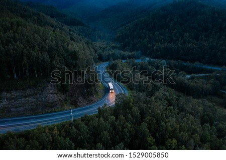 Aerial view of a sharp turn on a mountain road among green forest trees. Semi truck with cargo trailer and bright headlights on a dark highway. P-258 road near Baikal shore in Siberia, Russia #1529005850