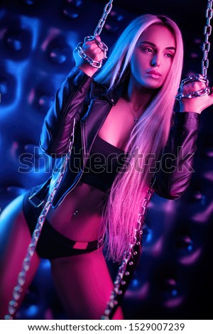 beautiful stylish fashionable girl in bodysuit posing in photo Studio on dark background with chains in neon light #1529007239