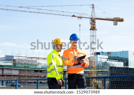 Male Architect Giving Instructions To His Foreman On Clipboard Working At Construction Site #1529073989