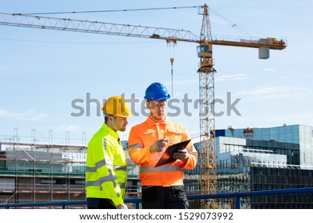 Male Architect Giving Instructions To His Foreman On Clipboard Working At Construction Site #1529073992