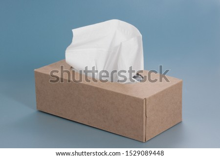 Nice brown tissue paper box on blue background Royalty-Free Stock Photo #1529089448