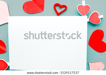 Valentine's Day composition - handmade hearts and white paper blank on blue background #1529117537