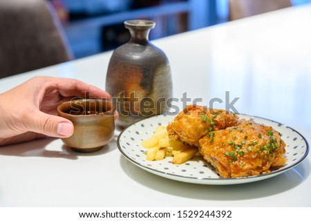 A man's hand is raising a sake cup to drink, a white table with fried chicken and potatoes in a polka dot dish. Is a Japanese style meal. #1529244392