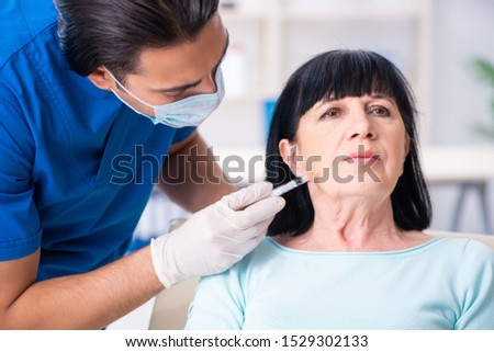 Old woman visiting male doctor for plastic surgery #1529302133