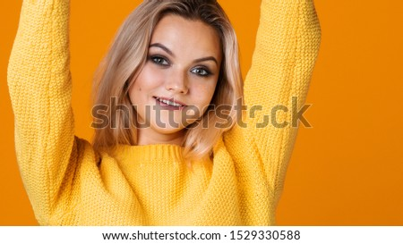 Happy and cheerful blonde in a yellow sweater on a yellow background. Positive young woman rejoices and dances, portrait close-up. copy space #1529330588
