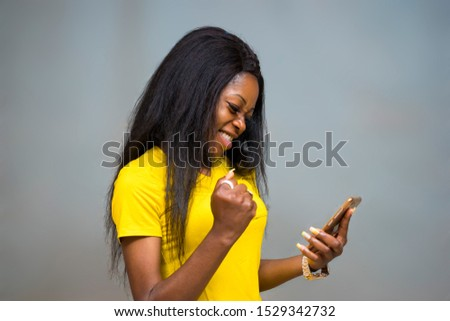 satisfied Young African hipster girl,types text message on cell phone, enjoys online communication, types feedback, wears yellow shirt, isolated on Gray studio wall. Technology concept   #1529342732
