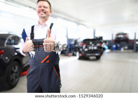 Focus on hand of happy engineer man showing thumb up and standing in modern car maintenance garage with automobiles. Machinery repairman concept. Blurred background #1529346020