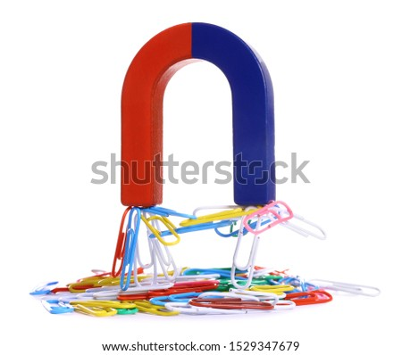 Horseshoe magnet attracting paper clips on white background