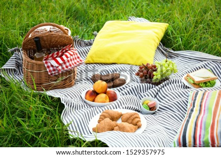 Picnic blanket with different snacks on green grass #1529357975