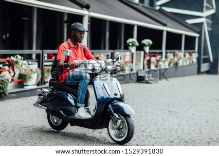 Happy man courier poses on fast motorbike, carries rucksack, wears helmet, looks aside with pleased expression. People, technology, transport. #1529391830