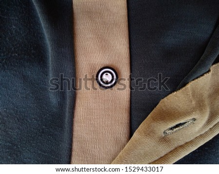 Close up of black shirt with button. #1529433017