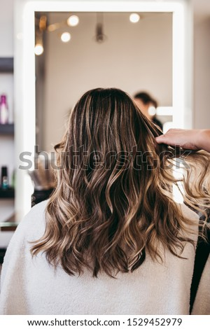 Beautiful brunette woman with long hair at the beauty salon getting a hair blowing. Hair salon styling concept. #1529452979