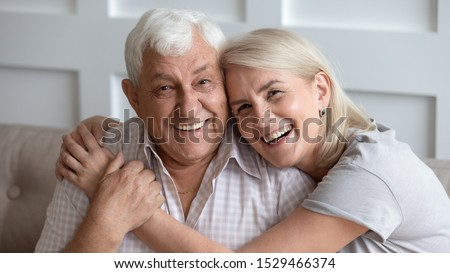 Horizontal banner happy old couple in love seated on couch embracing, laughing grey haired husband and wife pose looks at camera, elderly family portrait, long life marriage, sincere feelings concept #1529466374