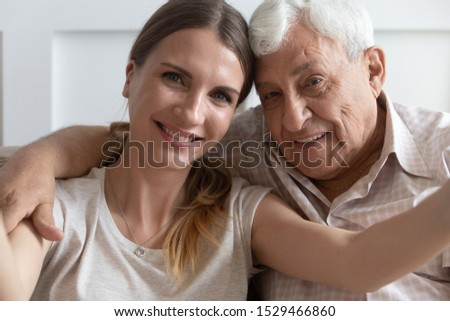Close up faces of elderly 80s grandfather adult 30s granddaughter hands holding camera smiling make self portrait webcam view, older younger generations relatives people taking photo or record video #1529466860