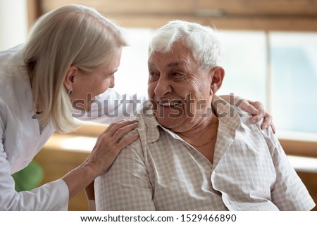 Caring middle-aged female licensed practical nurse in white coat talk to elderly patient 80s man, worker care about old healthcare consumer listens complaints give support, caregiving service concept #1529466890