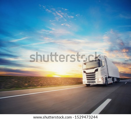 European truck vehicle on motorway with dramatic sunset light. Cargo transportation and supply theme. #1529473244