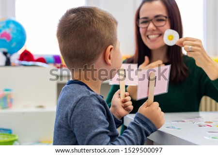 Children speech therapy concept. Preschooler practicing correct pronunciation with a female speech therapist. Royalty-Free Stock Photo #1529500097