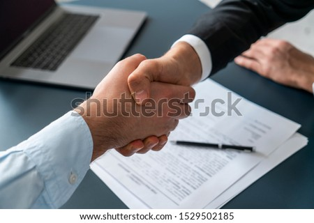 Close up of two businessmen shaking hands in blurred office with computer and contract on table. Concept of partnership and communication #1529502185