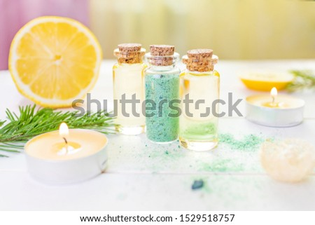 The concept of aromatherapy, relaxation, organics. Transparent bottles with aromatic oil and sea salt, spruce branch, lemon, candles on a light wooden background. Organic Apothecary #1529518757
